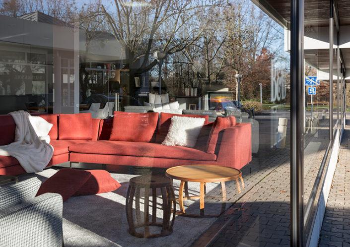 Blick durch die Scheibe auf ein rotes Sofa bei MEISER HOME OF LIVING